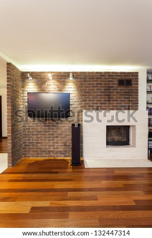 Spacious apartment - brick wall with fireplace and tv - stock photo