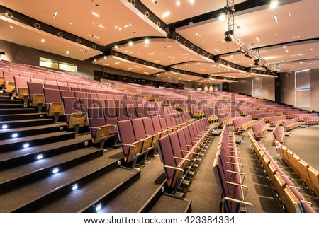 Spacious auditorium with rows of chairs and stairs - stock photo