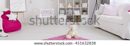 Spacious baby room with white cradle, sofa, shelving unit and pink sack chair - stock photo