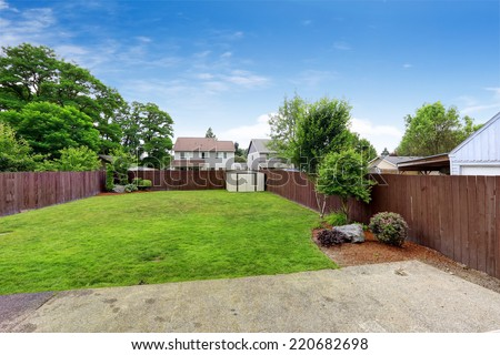 Spacious backyard area with  dark brown wooden fence and shed. View from patio area - stock photo