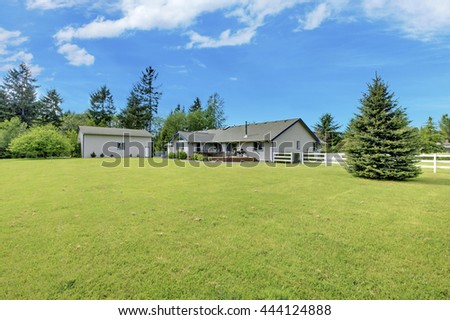 Spacious backyard garden with green lawn, shed and white wooden fence.