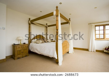 Spacious bedroom minimialistic with four poster bed - stock photo