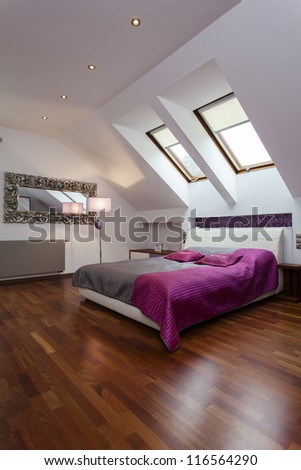 Spacious bedroom with purple and silver bed - stock photo