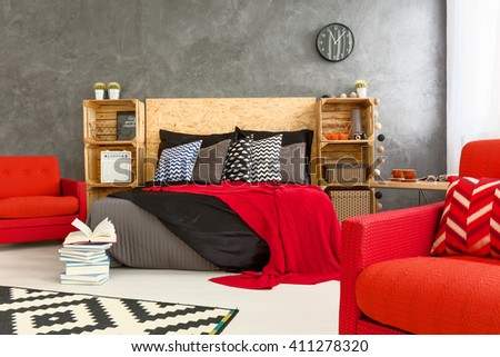 Spacious bedrooom in grey with stylish, red details