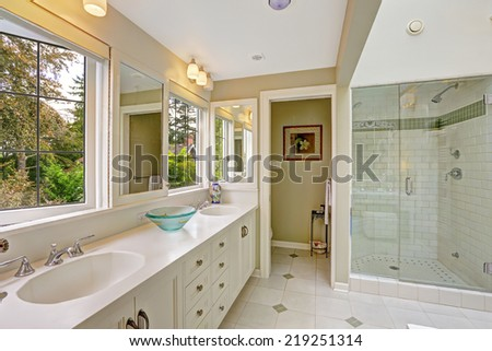 Spacious bright bathroom with white storage combination and glass door shower - stock photo