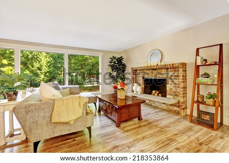 Spacious bright living room with brick fireplace, couch, wooden coffee table and glass wall - stock photo