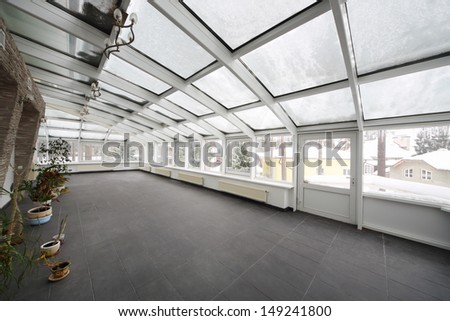 Spacious conservatory with small number of plants in cottage at winter. - stock photo