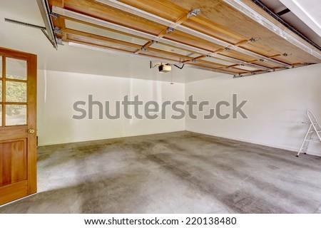 Spacious empty garage interior with open automatic door - stock photo