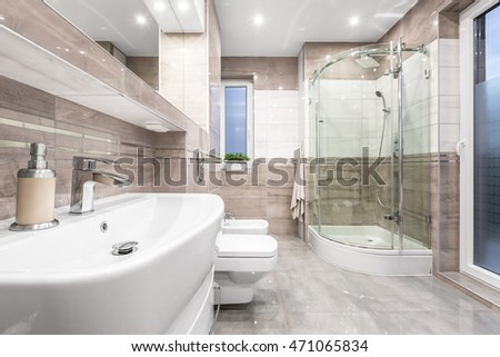 Spacious high gloss bathroom in beige with basin, mirror, toilet, bidet and shower