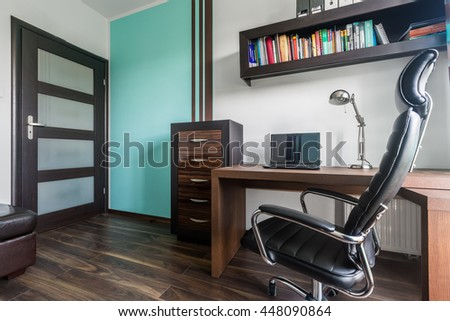 Spacious home office with dark brown furniture, comfortable chair and decorative turquoise wall detail - stock photo