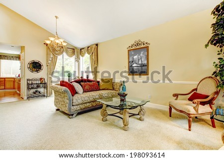 Spacious ivory living room with high vaulted ceiling and carpet floor. Furnished with antique sofa and glass top table with stone legs - stock photo
