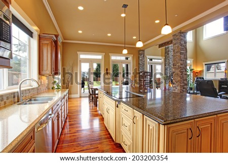 Spacious kitchen interior with kitchen island and dining area in luxury house - stock photo