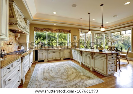Spacious kitchen room with antique storage combination. View of beautiful dining table set with flowers.