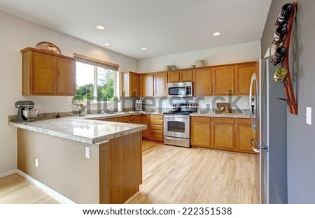 Spacious kitchen room with granite tops, steel stainless appliances and new hardwood floor - stock photo