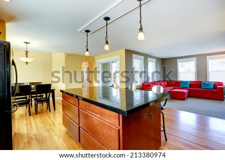 Spacious kitchen room with kitchen island and stools. Dining area with black rustic table and chairs