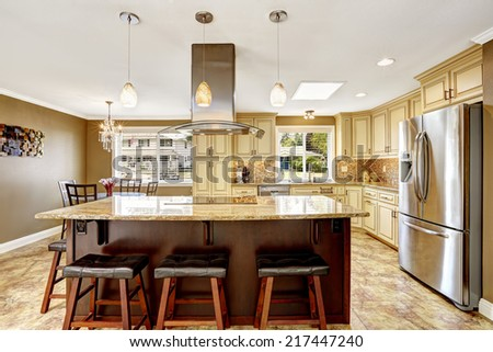 Spacious kitchen room with tile back splash trim and tile floor. Big kitchen island with built-in stove, granite top and steel hood - stock photo