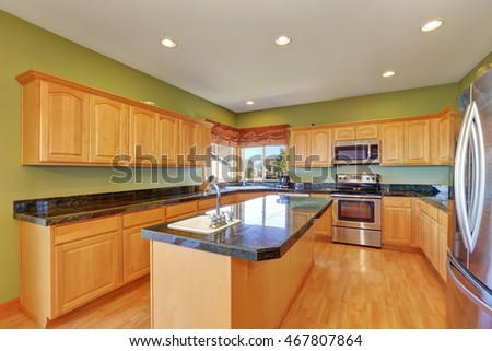 Spacious kitchen with green walls and hardwood floor. Has stainless steel appliances, kitchen island, maple storage combination and granite counter tops. Northwest, USA