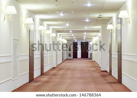 Spacious light hallway with many doors leading into hotel rooms. - stock photo