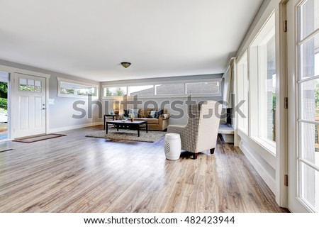 Spacious living room interior with polished hardwood floor, rug and dark brown coffee table. Northwest, USA