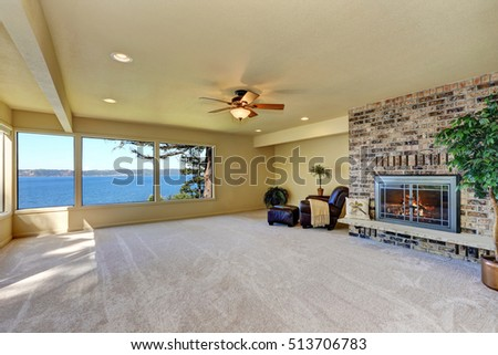 Spacious living room with carpet floor and brick wall trim with fireplace. Northwest, USA
