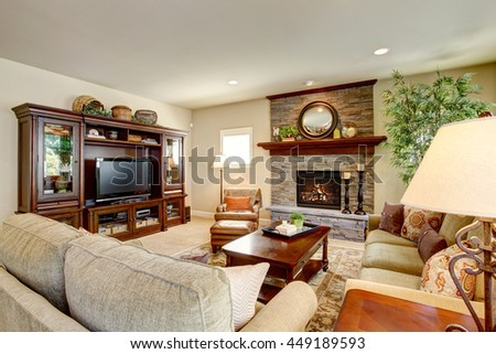 Spacious living room with fireplace, carpet floor and wooden furniture. There are two green sofas and leather brown armchair