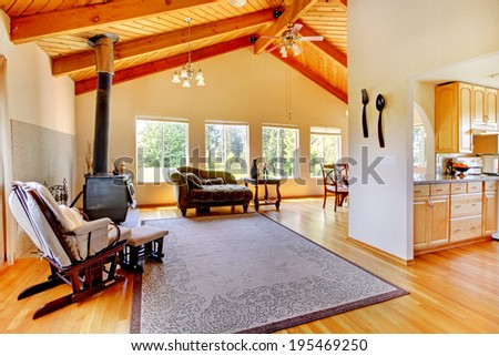 Spacious living room with hardwood floor, antique green sofas, wooden coffee table and office area - stock photo
