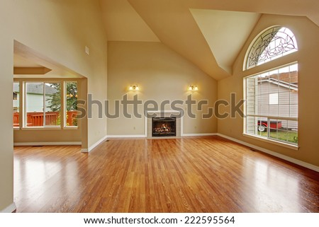 Spacious living room with high ceiling, big arch window, fireplace and new hardwood floor in empty new house - stock photo
