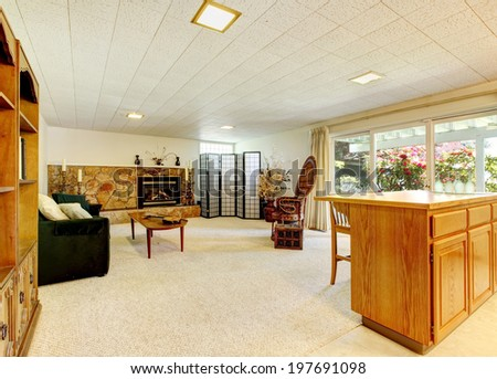 Spacious living room with stone background fireplace, black sofa, privacy screen and antique cabinet