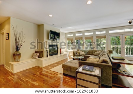 Spacious living room with walkout deck. View of couch with coffee table, fireplace and TV