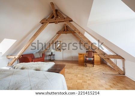 Spacious loft bedroom interior in a roof apex viewed from the bed showing exposed roof timbers, a wooden parquet floor and desk - stock photo
