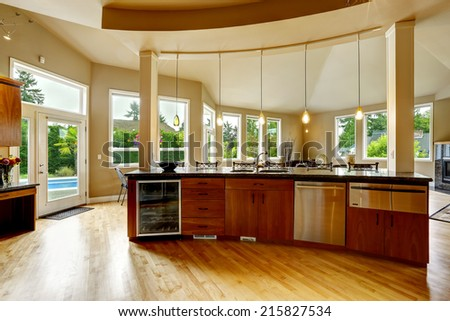 Spacious luxury kitchen room with round kitchen island and steel appliances
