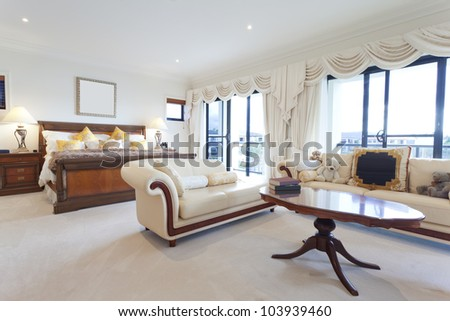 Spacious master bedroom in luxury house overlooking the water - stock photo