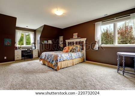 Spacious master bedroom interior with soft carpet floor and dark brown walls. Room has small office area by the window - stock photo
