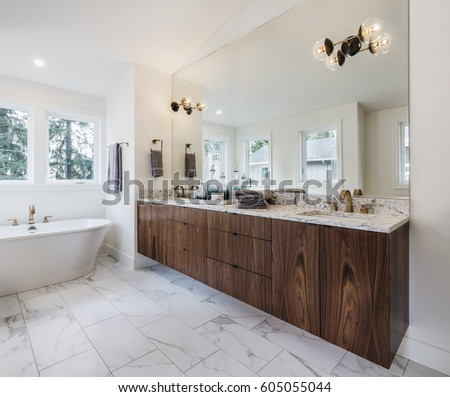 Spacious modern bathroom, bright and airy with deep soaking tub, sideview