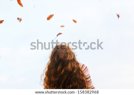 Spacious rear view of a child girl with red curly hair tilting her head back and looking up to the sky with dry autumn leaves floating and falling down, outdoors. - stock photo