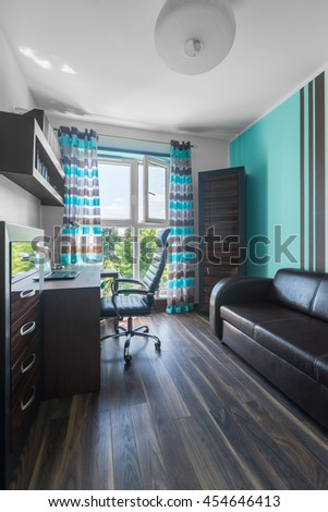 Spacious room in brown and turquoise with wooden furniture, armchair and leather sofa