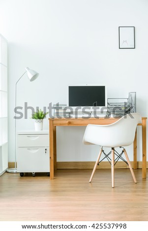 Spacious room with wooden floor with small space for work. By the wall wooden table with computer - stock photo