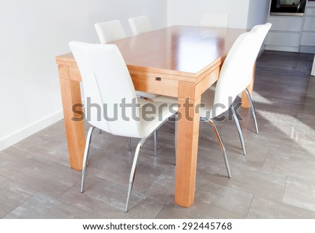 Spacious room with wooden table and white chairs - stock photo