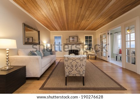 Spacious sitting area in living room in modern sumptuous style home wooden ceiling and floors  - stock photo