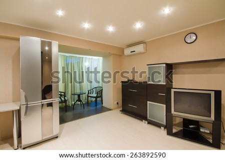 Spacious studio apartment with an open balcony. Classic style interior - stock photo