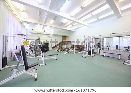 Spacious well lit empty gym with special equipment for physical training - stock photo