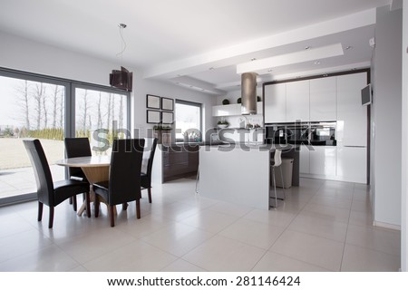 Spacious white kitchen connected with dining hall - stock photo