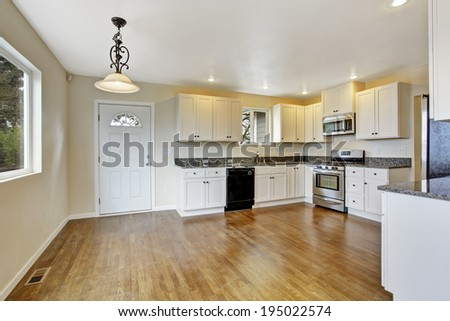Spacious white kitchen room with steel appliances, hardwood floor
