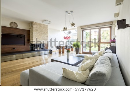 spacious wooden lounge with big television fireplace and comfortable couch