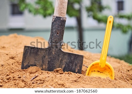 Spade and toy shovel in the sand - stock photo
