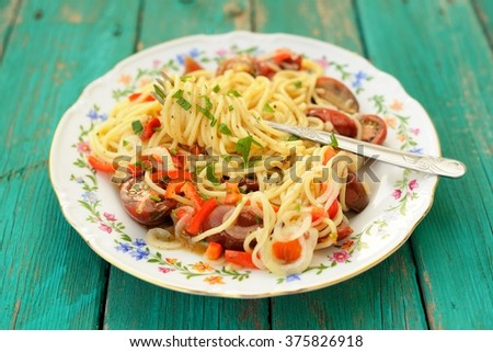 Spaghetti al Pomodoro in white plate with fork on wooden turquoise table top view closeup