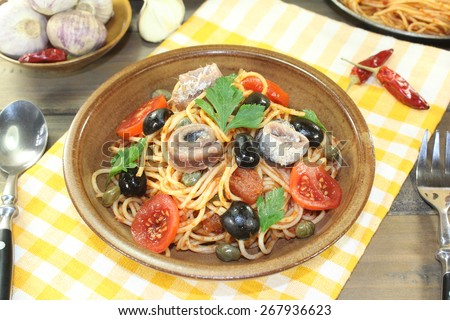Spaghetti alla puttanesca with olives, capers and anchovies on a napkin