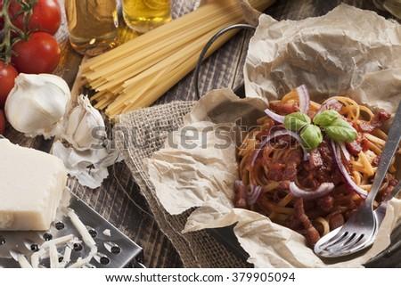 spaghetti amatriciana italian basic food tomato onion garlic bacon dish on vintage table - stock photo
