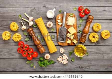 Spaghetti and fettuccine with ingredients for cooking pasta on a wooden table, top view. Flat lay - stock photo