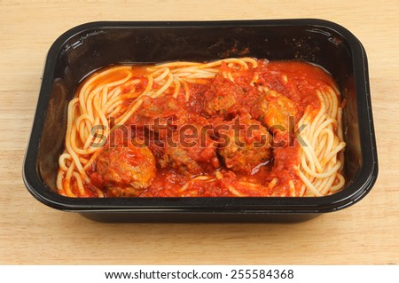 Spaghetti and meatballs in a plastic carton on a wooden board - stock photo